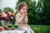 Malá holčička jí čokoládový dort v přírodě na pikniku. Koncept šťastného dětství
