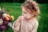 Malá holčička jí čokoládový dort v přírodě na pikniku