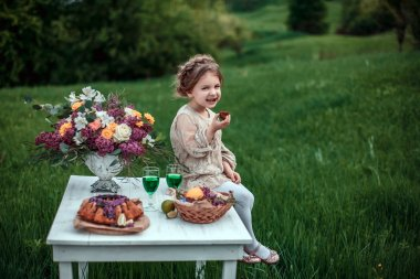 Little baby girl eats chocolate cake in nature at a picnic.