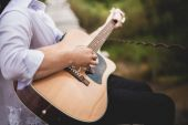 Young man with acoustic guitar in park
