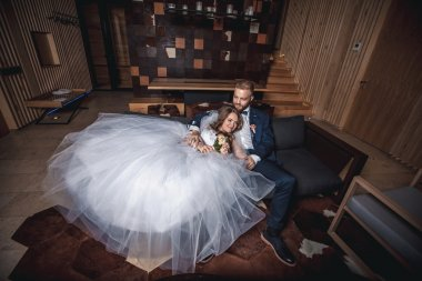 Happy bride and groom  sitting on couch