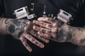 Man tattoo artist with tattoo machines