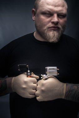 Man tattoo artist with tattoo machine