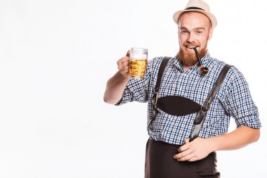 Happy smiling man with leather trousers (lederhose) holds oktoberfest beer glass