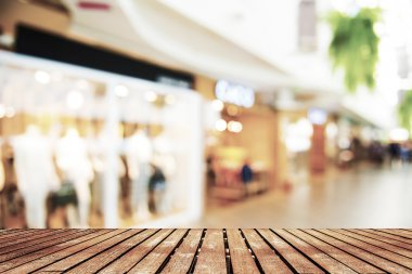 Perspective wood and blurred shopping mall with bokeh light background.
