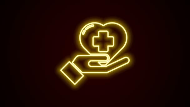 Ragyogó neon vonal Szív egy kereszt ikon elszigetelt fekete háttérrel. Elsősegély. Egészségügyi, orvosi és gyógyszertári jelek. 4K Videó mozgás grafikus animáció