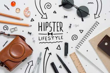 Photo of hipster workplace with lots of stationery objects and g