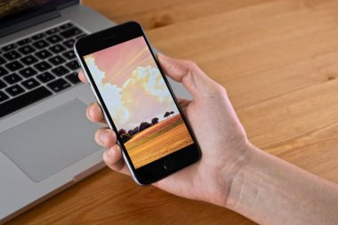 iPhone 6 hold in hand with a Macbook