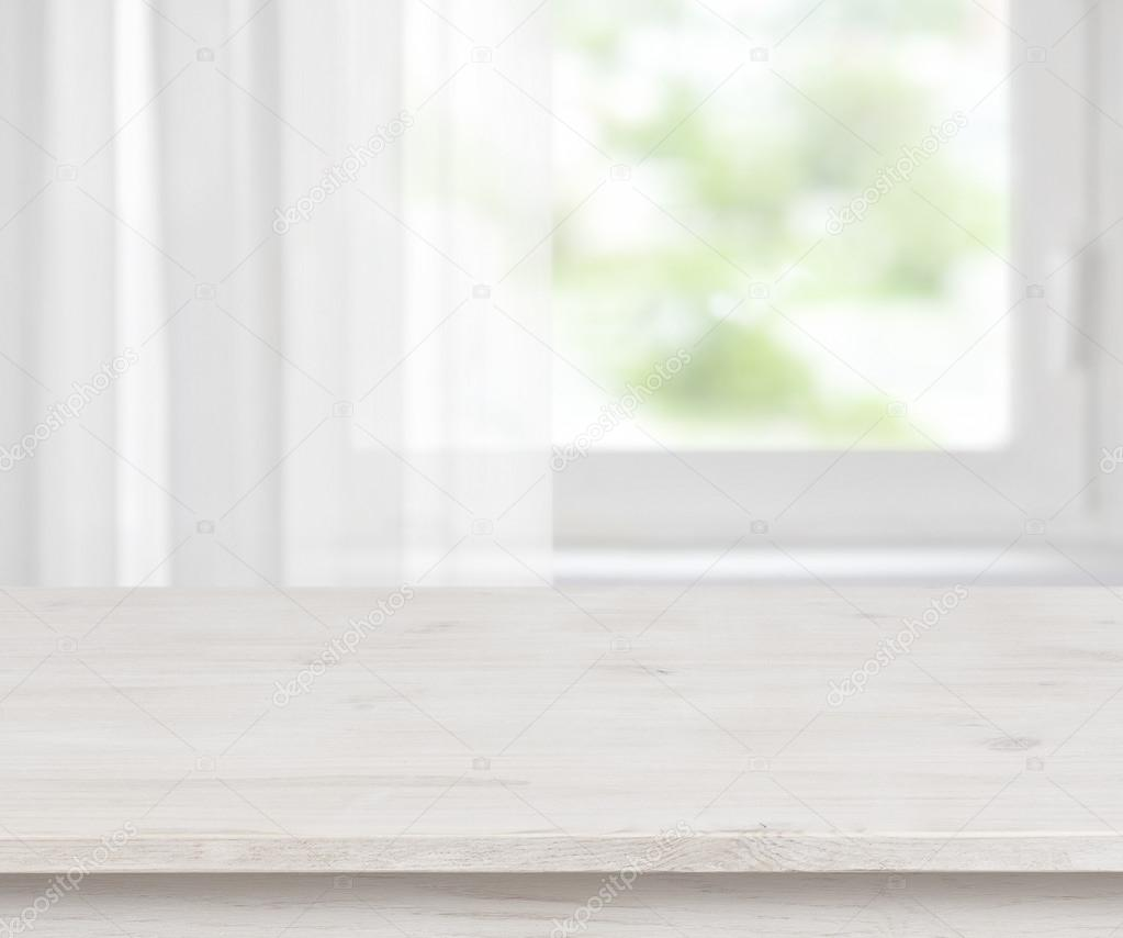 Wooden table surface on defocused half curtained window for Table background