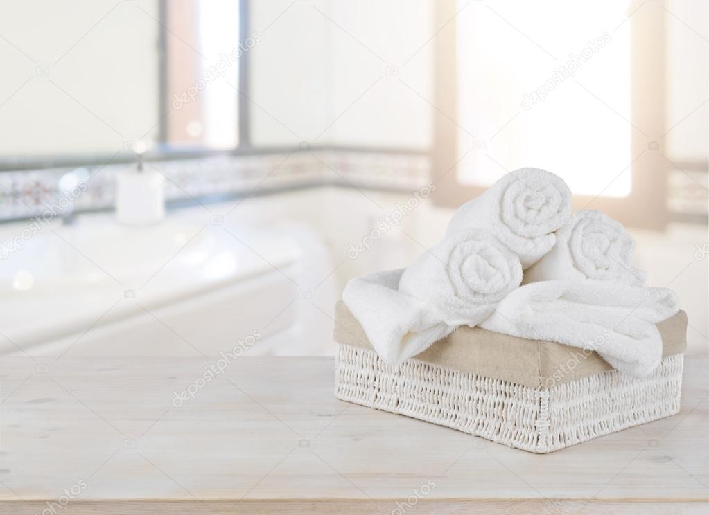Towels In Basket On Wooden Table Over Defocused Bathroom Background Stock Photo