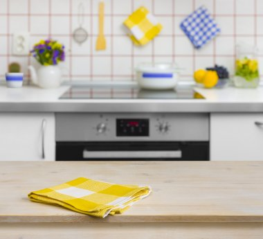 Wooden table with yellow napkin on kitchen background