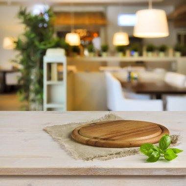 Cutting board on table over blurred restaurant interior background