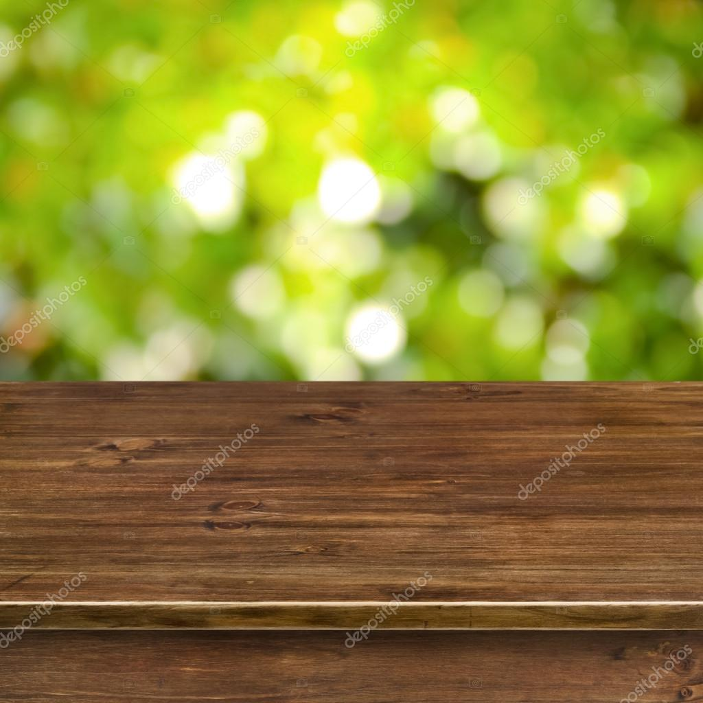 Green bokeh lights background with wooden table