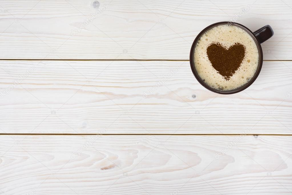 Top view of coffee cup with heart on wooden background
