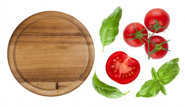 Top view of isolated cutting board with tomato and basil