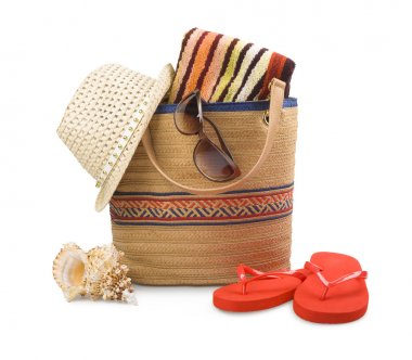 Beach bag and towel with sunbathing accessories isolated on white