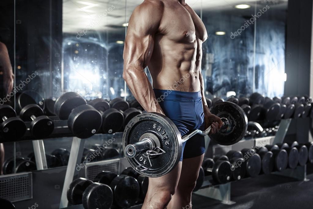 Muscular bodybuilder guy doing exercises with barbells