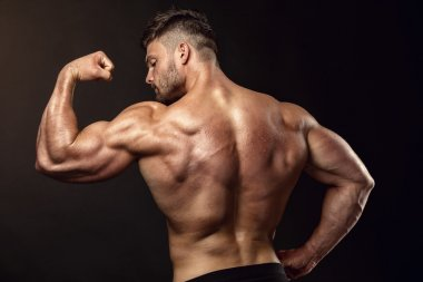 Strong Athletic Man Fitness Model posing back muscles, triceps,