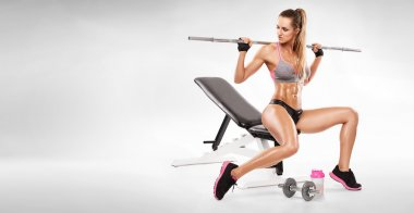 Nice sexy woman sitting on a bench and doing workout with dumbbell