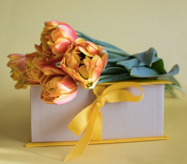 Orange-red fresh tulips in a bouquet and a gift box on a yellow background. Greetings, celebration, romance concept. Bright colorful postcard for congratulations on all holidays and events