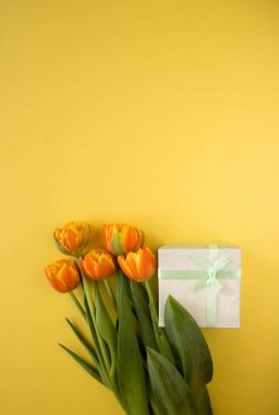 Orange-red fresh tulips in a bouquet and a gift box on a yellow background. Greetings, celebration, romance concept. Copy space for your text. Bright colorful postcard for congratulations on all holidays and events