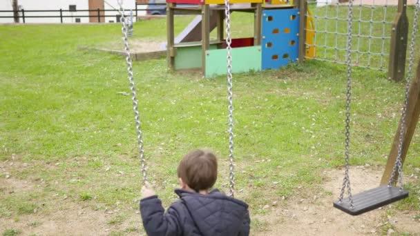 Baby Kleinkind auf der Park-Schaukel schwingt