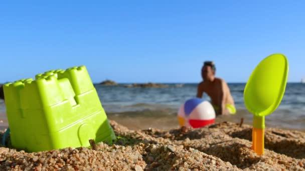 Otec a syn hraje míč na pláži