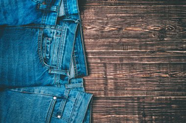 Blue jeans on a brown wooden background.