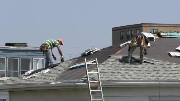 Arbeiter bringen neue Dachziegel an