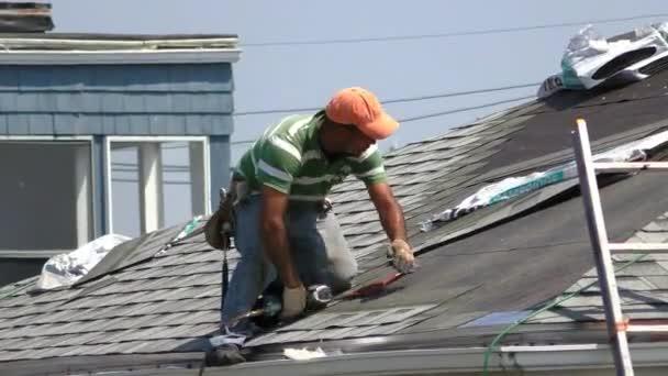 Arbeiter bringt neue Dachziegel an