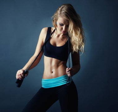 Portrait of attractive sexy fitness blond girl with jumping rope