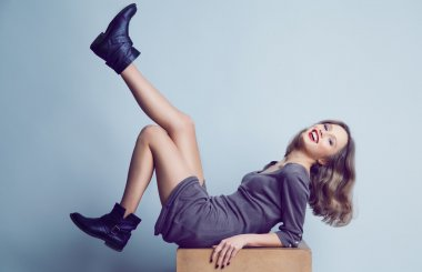 Smiling young womanl in trendy boots and dress posing in studio.