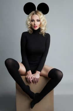 Sexy blond woman in black t-shirt and gaiters in Mickey Mouse lo