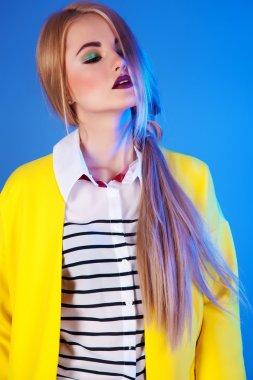 Fashion portrait of blond woman in trendy yellow jacket over blu