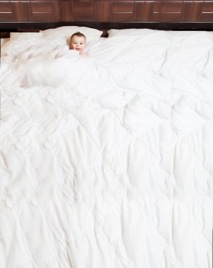 Fanny and cute baby smiling under blanket in large bed. Copy spa