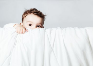 Cute and funny baby is looking and climbing on blanket over whit