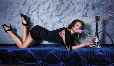 Sexy party woman smoking hookah in night club.