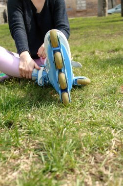 Girl wears roller skates sitting on the grass