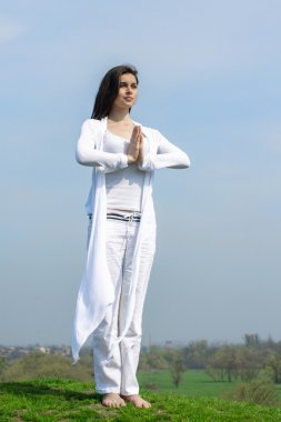 Girl doing yoga exercise standing on a hill