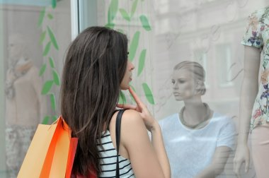Side view of a girl looks at a glass shop window.