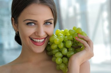 Woman posing with a bunch of grapes and smiling.
