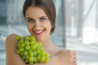Beautiful turkish woman holding a bunch of grapes