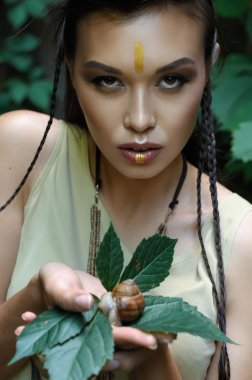 Girl holding a snail in her hands.