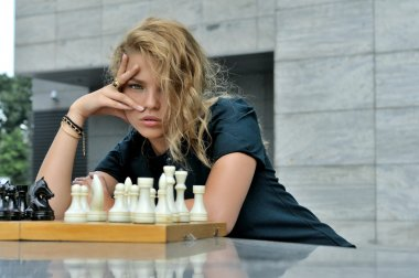 Woman sitting on the contrary chess pieces