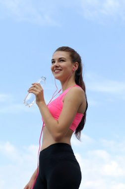 Bottom view of a girl in sportswear drinks water