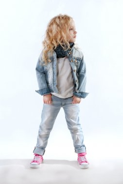 Little girl in denim suit and pink sneakers looking away