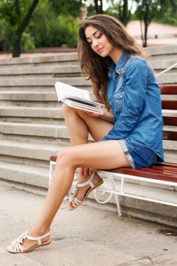 Girl reads a book while sitting on a bench against the backgroun