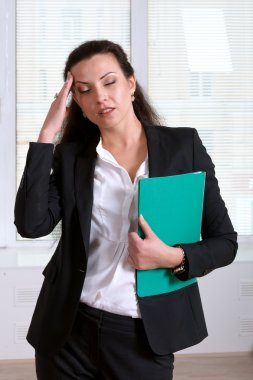 Woman suffering from illness or headache holding her head