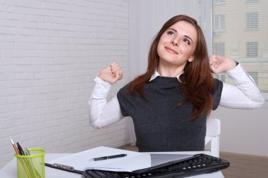 Girl at the workplace tired of work stretches