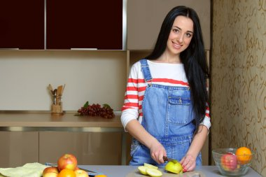 Brunette housewife in blue overalls cuts an apple in the kitchen